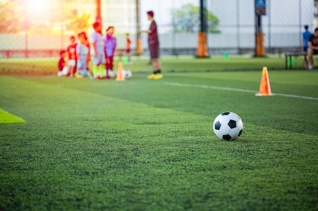Cono di tattiche di pallone da calcio sul campo in erba con sfondo di allenamento