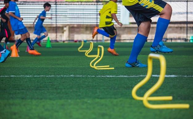 Tattiche di pallone da calcio sul campo in erba con cono barriera per addestrare i bambini a saltare l'abilità nell'accademia di calcio