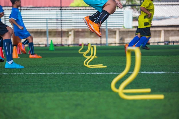 Tattiche di pallone da calcio sul campo in erba con cono di barriera per addestrare i bambini a saltare l'abilità nell'accademia di calcio