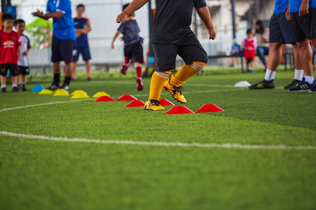 Tattiche di pallone da calcio sul campo in erba con barriera per addestrare i bambini a saltare l'abilità nell'accademia di calcio