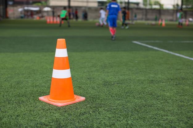 Tattiche del pallone da calcio sul campo in erba con cono per lo sfondo dell'allenamento