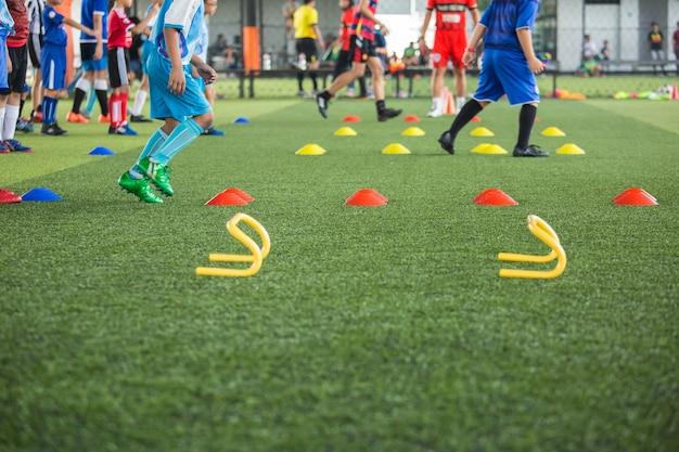 Tattiche di pallone da calcio sul campo in erba con cono per addestrare i bambini a saltare l'abilità nell'accademia di calcio