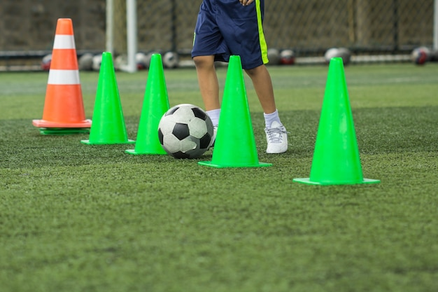 Tattiche di pallone da calcio sul campo in erba con cono per l'allenamento della thailandia in background