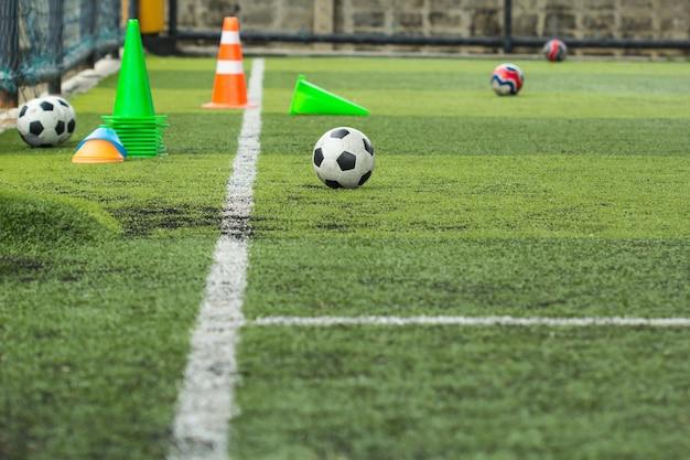 Tattiche di pallone da calcio sul campo in erba con cono per l'allenamento