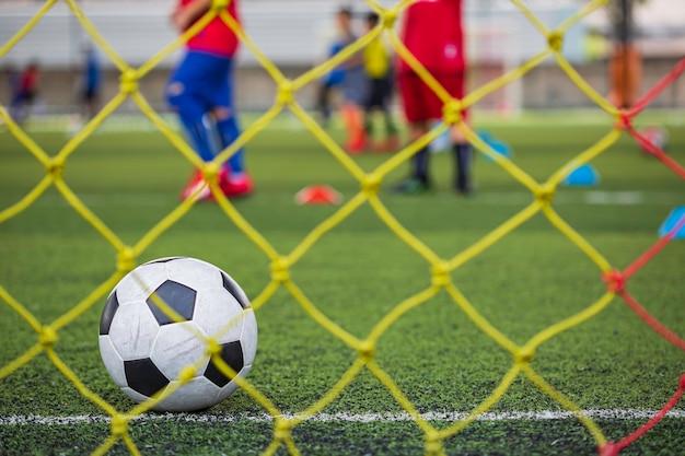 Tattiche di pallone da calcio sul campo in erba con rete per allenare le abilità dei bambini nell'accademia di calcio