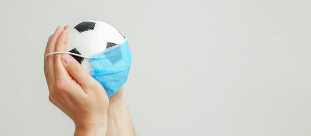 Pallone da calcio con una mascherina medica