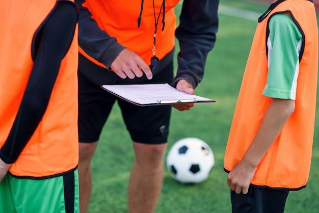 L'allenatore di calcio mostra una strategia di gioco del calcio ai suoi giocatori durante l'allenamento.