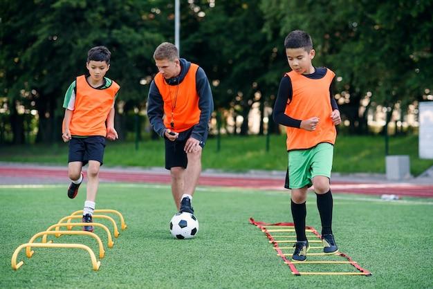 L'allenatore di calcio osserva i suoi alunni mentre fanno esercizi di corsa con il superamento degli ostacoli