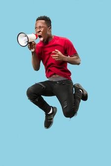 Tifoso di calcio che salta su sfondo arancione. il giovane africano come tifoso con megafono isolato su studio blu. concetto di supporto. emozioni umane, concetti di espressione facciale.