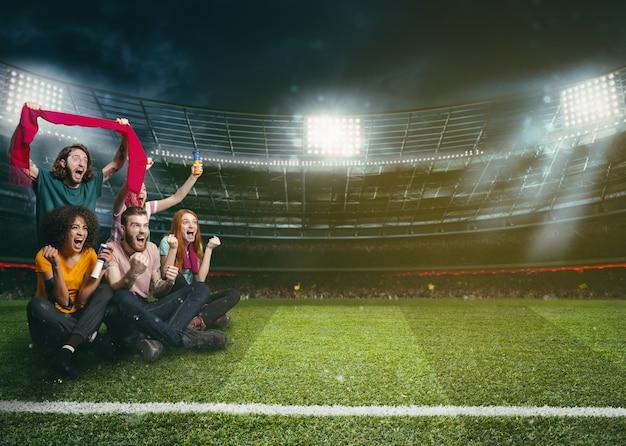 Tifosi di calcio nel bel mezzo dell'azione durante una partita notturna allo stadio