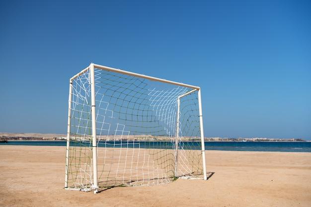 Porta di calcio o di calcio con rete sul cielo blu della spiaggia di sabbia e sullo sfondo del paesaggio del mare. concetto di intrattenimento di località di mare. attività estive e sport. attività di pioppo beach football. rilassati e divertiti.
