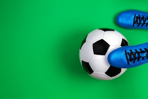 Giocatore di gioco del calcio di calcio con pallone da calcio su priorità bassa verde