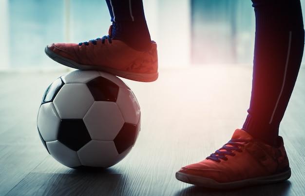 Soccer kid piedi che calpestano un pallone da calcio per lo sport indoor giovanile.