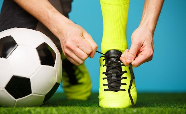 Giocatore di calcio che si prepara per il gioco allacciandosi le scarpe.