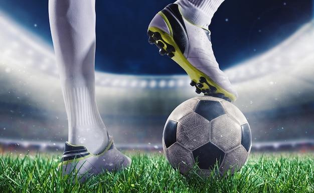 Giocatore di calcio con pallone da calcio sul prato di uno stadio pronto per la partita