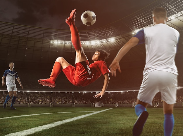 L'attaccante di calcio in uniforme rossa colpisce la palla con un calcio acrobatico in aria allo stadio