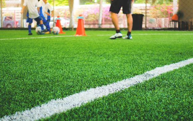 Linea bianca del campo di addestramento di calcio con addestramento del bambino nel fondo