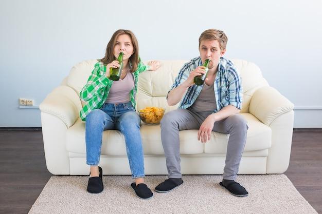 Concetto di coppa del mondo di calcio - coppia moderna che sembra eccitata e felice di guardare il gioco sportivo in tv