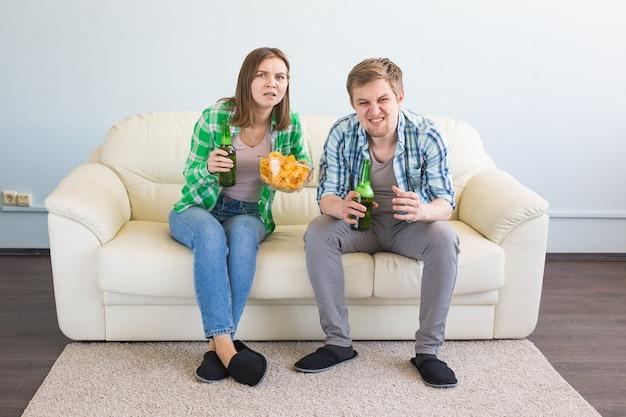 Concetto di coppa del mondo di calcio. coppia moderna che sembra eccitata e felice guardando il gioco di sport in tv
