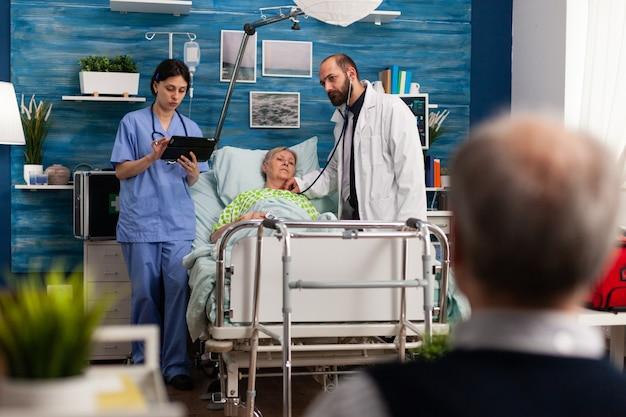 L'assistente sociale ascolta il suono dei polmoni usando lo stetoscopio medico