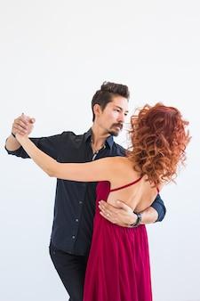 Danza sociale, bachata, kizomba, salsa, concetto di tango - donna vestita in abito rosso e uomo in nero
