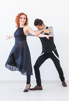 Danza sociale, bachata, kizomba, tango, salsa, concetto di persone - giovani coppie che ballano sopra bianco