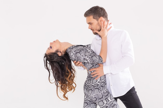 Danza sociale, bachata, kizomba, zouk, concetto di tango - l'uomo abbraccia la donna mentre balla su bianco