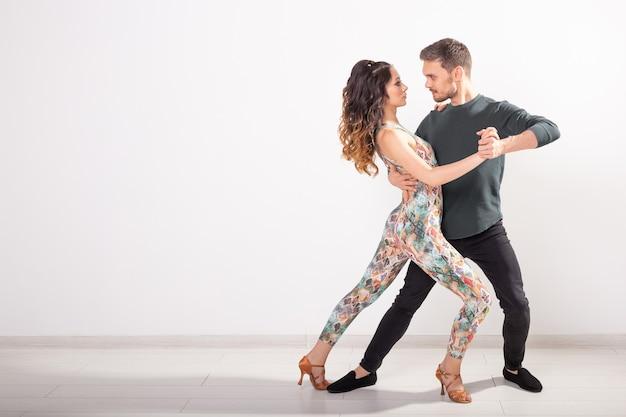 Danza sociale, bachata, salsa, kizomba, zouk, concetto di tango - l'uomo abbraccia la donna mentre balla su bianco