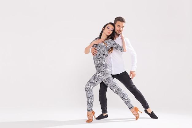 Concetto di ballo sociale - adulti felici attivi che ballano bachata o salsa insieme su una superficie bianca