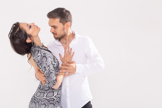 Concetto di ballo sociale - adulti felici attivi che ballano bachata o salsa insieme sopra il muro bianco con lo spazio della copia