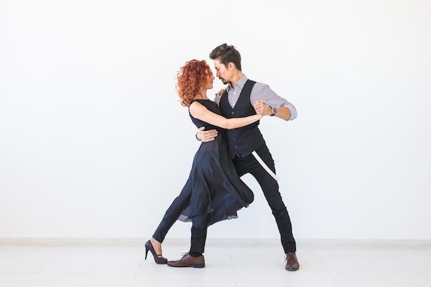 Danza sociale, kizomba, tango, salsa, concetto di persone - belle coppie che ballano bachata sulla parete bianca con lo spazio della copia