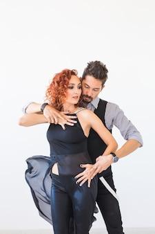 Danza sociale, salsa, zouk, tango, concetto di kizomba - belle coppie che ballano bachata su bianco