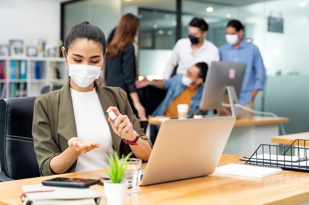 La distanza sociale in ufficio con il team di lavoro che indossa maschere facciali