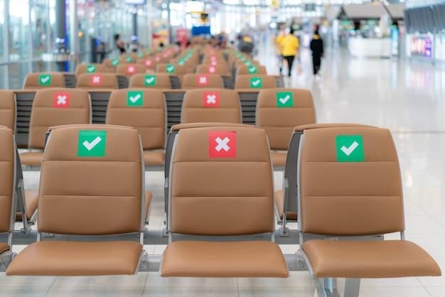 Disposizione della sedia pubblica a distanza sociale durante la situazione covid-19 in aeroporto