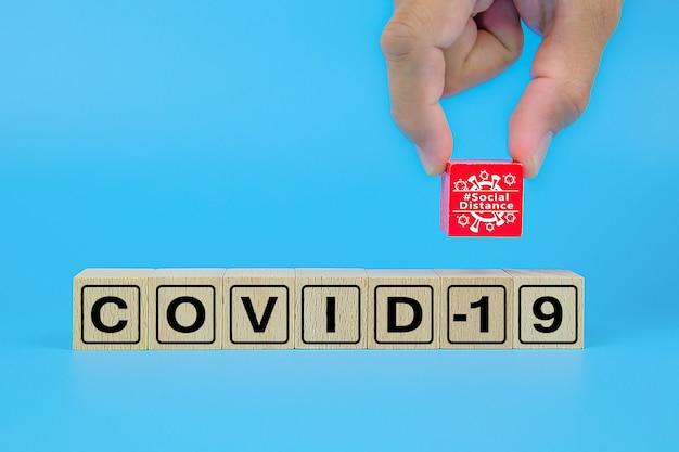 Distanza sociale con le icone di testo icona covid-19 sul blocco giocattolo in legno.