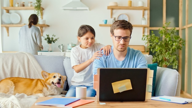 Riduzione dei contatti. un padre impegnato cerca di lavorare a distanza con il figlio e la moglie a casa.
