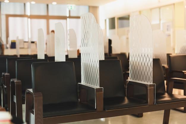 Sedia a distanza sociale con divisorio in acrilico nella sala d'attesa durante l'epidemia di covid-19.