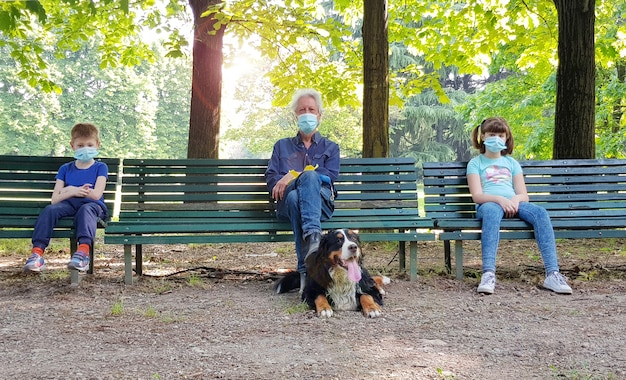 Distanziamento sociale: nonno e nipoti sono seduti sulle panchine del parco con maschere durante la pandemia di coronavirus