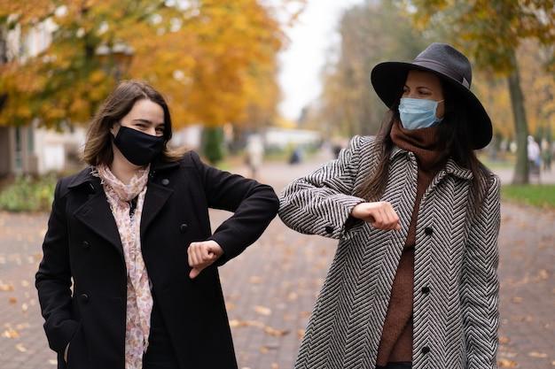 Il distacco sociale saluta con protuberanze sui gomiti per prevenire la diffusione del virus corona