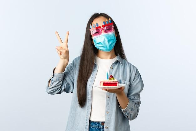Stile di vita a distanza sociale, pandemia di covid-19, celebra le vacanze sul concetto di coronavirus. felice ragazza asiatica b-day sorridente in maschera medica e occhiali da festa, con in mano la torta di compleanno e mostra il segno della pace