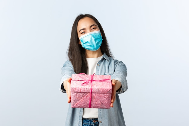 Stile di vita a distanza sociale, pandemia di covid-19, celebrazione delle vacanze durante il concetto di coronavirus. la donna asiatica felice allegra in maschera medica si congratula con l'amico con il compleanno, consegnando il regalo