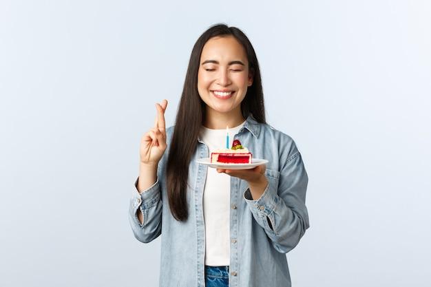 Stile di vita a distanza sociale, pandemia di covid-19, celebrazione delle vacanze durante il concetto di coronavirus. speranzoso felice compleanno ragazza asiatica chiude gli occhi e sorride mentre esprime il desiderio sulla torta di compleanno.