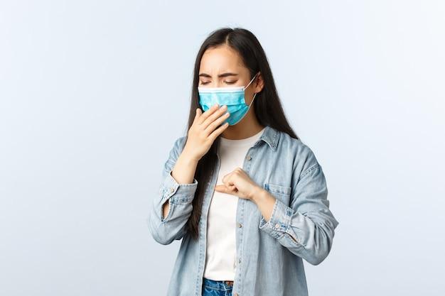 Stile di vita a distanza sociale, vita quotidiana pandemica covid-19 e concetto di tempo libero. ragazza asiatica con test positivo per il coronavirus che indossa una maschera medica e tossisce, essendo malata durante il blocco.