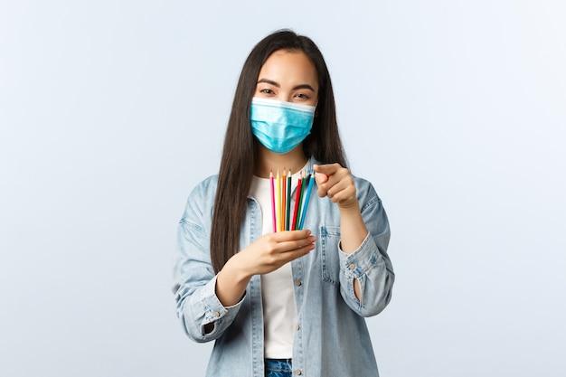 Stile di vita a distanza sociale, pandemia di covid-19, hobby di autoisolamento e concetto di tempo libero. eccitata donna asiatica in maschera medica guardando nuove matite colorate, impara a disegnare con i corsi online.