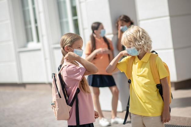 Riduzione dei contatti. scolari in maschere protettive nel cortile della scuola si salutano