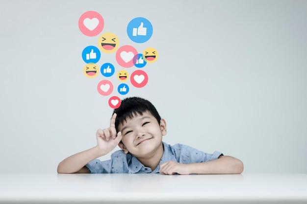 Social media e concetto online digitale, i bambini con la selezione di emoji sui social media. il concetto di vivere in vacanza e giocare sui social media. distanziamento sociale, concetto di lavoro da casa.