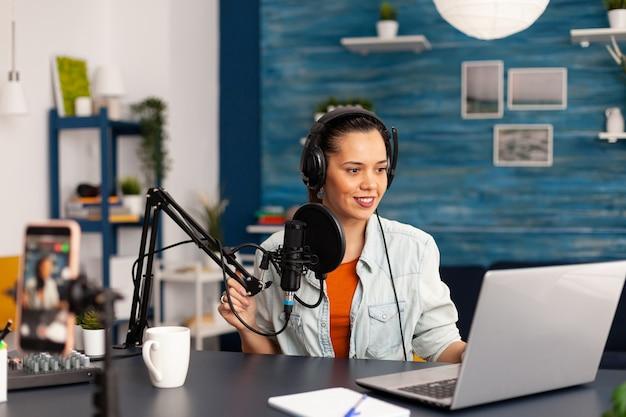 Influencer dei social media che discute del vlogging nel podcast di registrazione di home studio. nuova star dei media che crea contenuti di moda online con attrezzature professionali per il pubblico degli abbonati