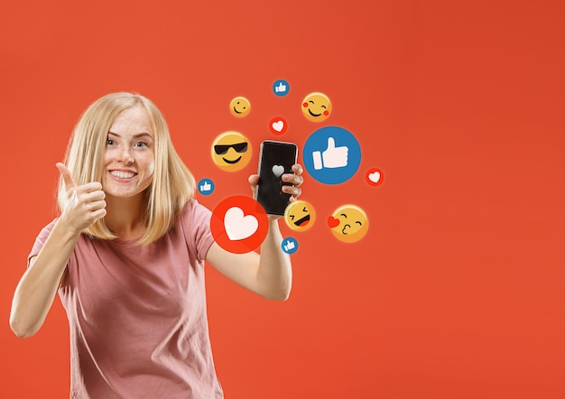 Interazioni sui social media sul cellulare. marketing digitale su internet, chat, commenti, mi piace. sorrisi e icone sopra lo schermo dello smartphone, quella tenuta da una giovane donna su sfondo rosso dello studio.