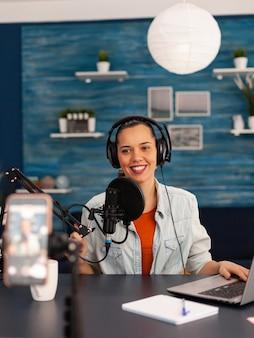Donna star dei social media che tiene in mano un microfono professionale durante la registrazione di podcast per il canale youtube. spettacolo online creativo produzione in onda trasmissione internet in diretta streaming video
