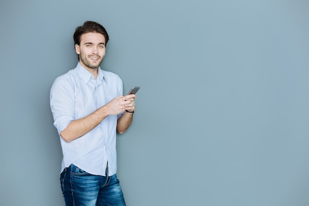 Social networking. felice giovane positivo che tiene il suo smartphone e lo utilizza mentre chatta sui social network